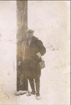 Frank I. Reed and one pole of an Anchorage Light and Power transmission line completed in 1928.
